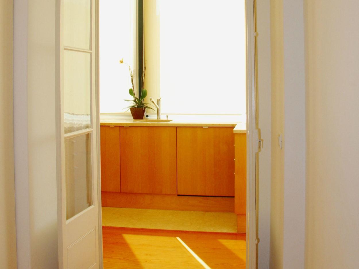 Corredor de acesso à Cozinha. Apartamento em Lisboa, Campo de Ourique, janelas de sacada com almofadas em vidro e madeira, pavimento em madeira e lioz.